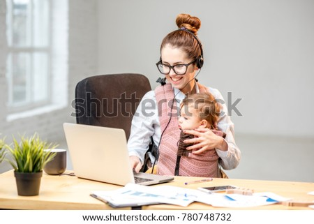 Multitasking businesswoman working with headset and laptop sitting with her baby son at the white office interior #780748732