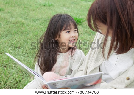 Japanese mother and child reading a book on the lawn