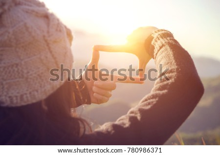 Future planning, Close up of woman hands making frame gesture with sunrise on mountain, Female capturing the sunrise, sunlight outdoor. Royalty-Free Stock Photo #780986371