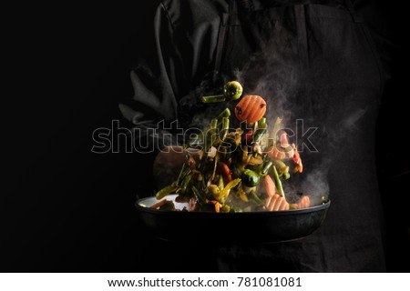 Chef cooking vegetables on a pan. Black background for copy text. Royalty-Free Stock Photo #781081081