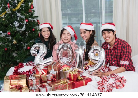 Group of friends celebrating Christmas at home and showing 2019 up, Christmas or New Year concept #781114837