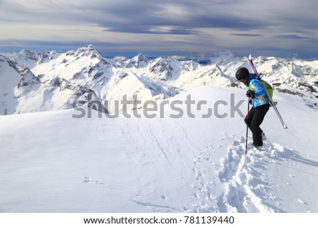 Snow covered summit and slier woman with skis on the backpack, Les Deux Alpes, France #781139440