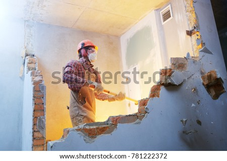 worker with sledgehammer at indoor wall destroying #781222372