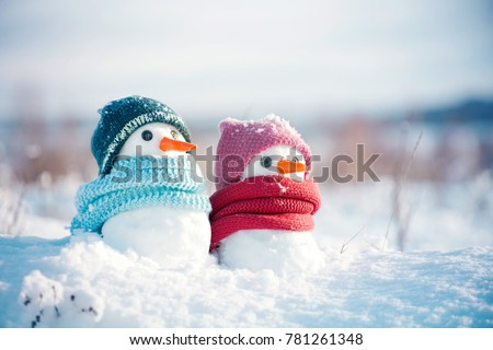Two little snowmen the girl and the boy in knitted caps and scarfs on snow in the winter. Festive background with a lovely snowman. Christmas card, copy space Royalty-Free Stock Photo #781261348