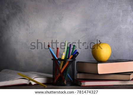 Group of school supplies and books on wooden table over a grey background #781474327