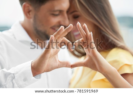 Beautiful Couple In Love Making Heart With Hands. Happy Smiling Young People Hugging, Showing Heart Shape With Hands And Enjoying Each Other Outdoors. Romantic Relationships. High Quality Image. Royalty-Free Stock Photo #781591969