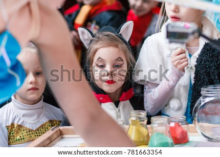 Kamenskoye, Ukraine - December 26, 2016: Christmas party for federation of cheerleading in Kamenskoye, child watches with interest as the girl draws on the sand #781663354