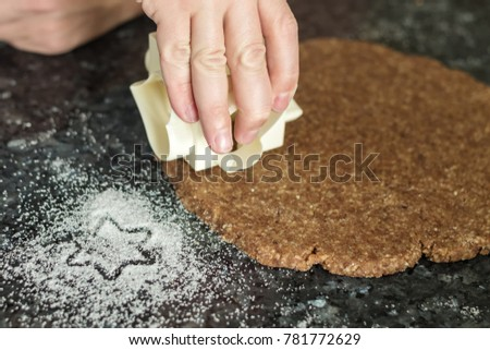 hand cut out the cinnamon stars on christmas dough #781772629