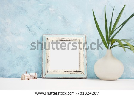 Square blue Photo frame mock up with green tropical plants in vaseand small wooden houses on shelf. Scandinavian style.  Text space #781824289