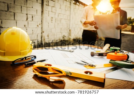 A desk of engineers who are studying the area for laying foundation of energy saving homes and raw material costs. Royalty-Free Stock Photo #781926757