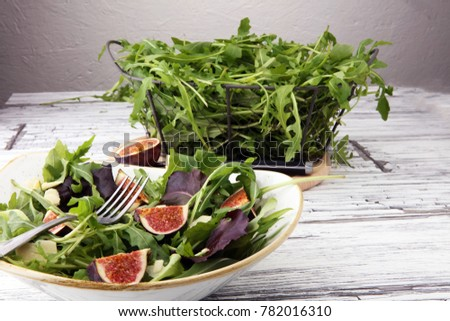 Autumn salad of arugula, figs in a white earthenware plate. #782016310