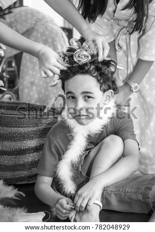Birthday party: black and white image of girls dressing up their little brother