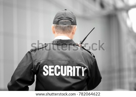 Male security guard using portable radio outdoors Royalty-Free Stock Photo #782064622
