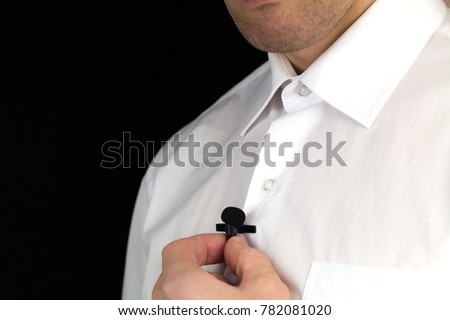 Man holds black lavalier microphone, interview