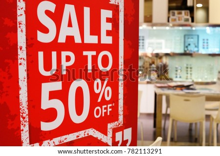 Sale up to 50% off text on a sign board inside a popular optic store  #782113291