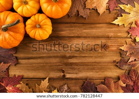 Pumpkins with fall leaves over wooden background. Top view.