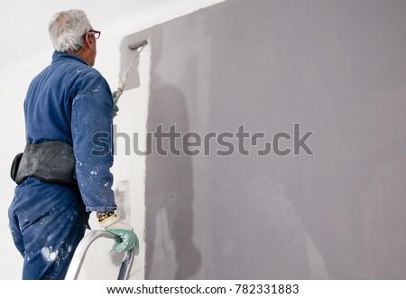 Senior man painting grey wall. Home renovation concept #782331883