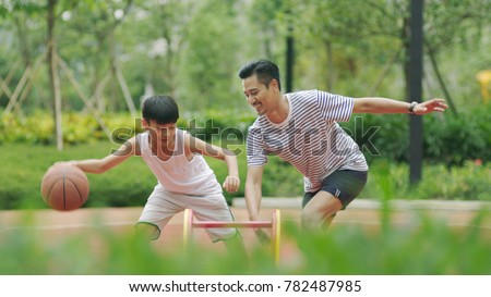 Asian father & son playing basketball in garden in morning #782487985