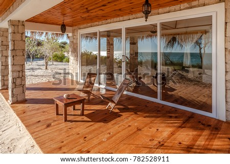 Terrace of a luxurious bungalow with reflection of the sea in the patio door #782528911