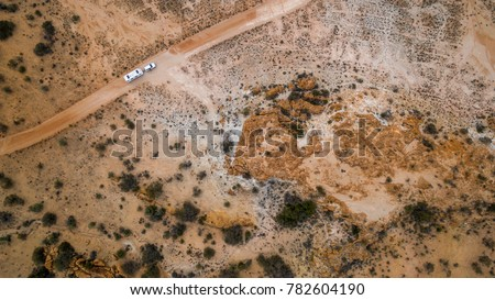 Aerial veiw of four wheel drive vehicle and large caravan on an outback road in Australia. #782604190