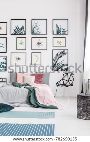 Colorful decor of a bedroom with a king-size bed, plants and posters #782650135