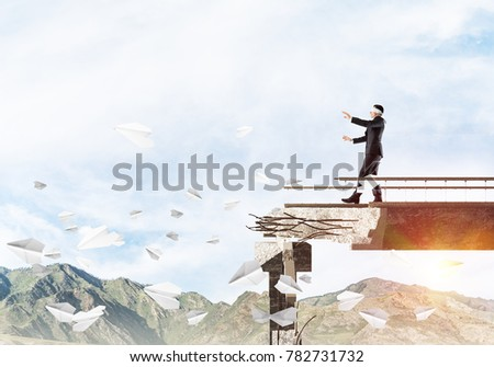Businessman walking blindfolded on concrete bridge with huge gap as symbol of hidden threats and risks. Skyscape and nature view on background. 3D rendering. #782731732