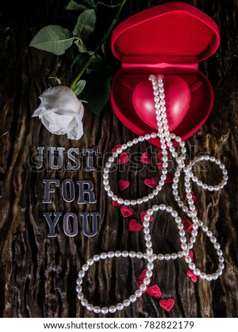 Image of arrangement for Valentine day with white rose and red heart shape model in heart shape box with pearl necklace on old wooden background and words of silver letter say just for you