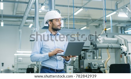 Chief Engineer in the Hard Hat Walks Through Light Modern Factory While Holding Laptop. Successful, Handsome Man in Modern Industrial Environment. Royalty-Free Stock Photo #782842939