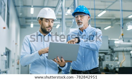 Head of the Project Holds Laptop and  Discusses Product Details with Chief Engineer while They Walk Through Modern Factory. Royalty-Free Stock Photo #782842951