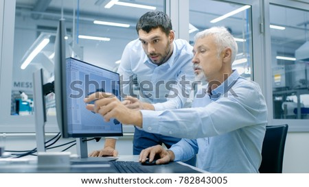 Industrial Designer Has Conversation with Senior Engineer While Working in CAD Program, Designing New Component. He Works on Personal Computer with Two Monitors. #782843005