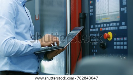 Chief Engineer/ Operator Programs/ Sets-up CNC Machine with Control Panel. He Works on the Modern Technologically Advanced Factory. Royalty-Free Stock Photo #782843047