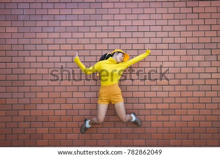 Portrait asian hipster girl on brick wall background,she wear yellow tone full body,Lifestyle of thailand people #782862049