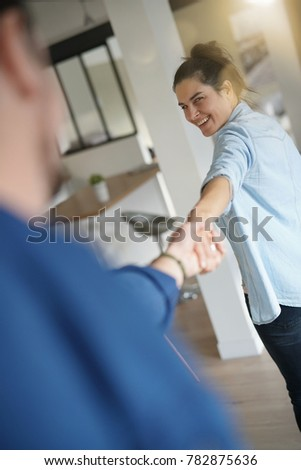 Woman pulling man's arm to follow her inside house #782875636