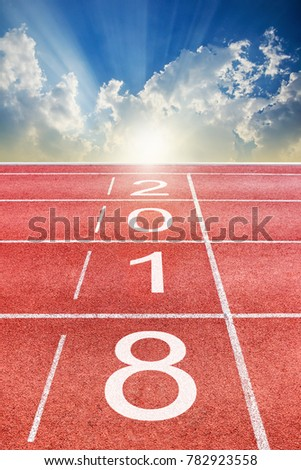 2018 Happy New Year text on athletics sport running track in the morning with sunrise sky and clouds #782923558
