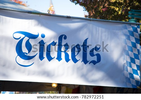 Large printed Ticket banner sign in German style, with Bavarian blue checker pattern, at the entrance booth for a Oktoberfest beer festival