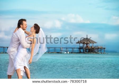 beautiful couple on the beach in wedding dress #78300718