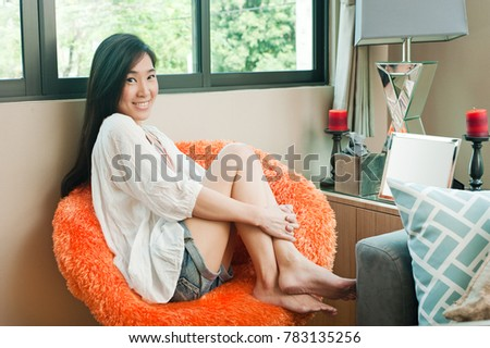 Asian woman is smiling and relaxing while sitting on sofa at home. #783135256