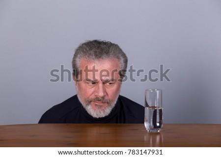 Man with glass half full, half empty, symbolic image #783147931