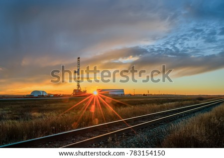Oil rig on the field at sunset with amazing cloudy sky, near the rail road in summer time