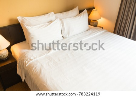 White comfortable pillow on bed with light lamp decoration interior of bedroom #783224119