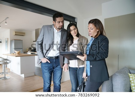 Couple with real-estate agent visiting modern house #783269092