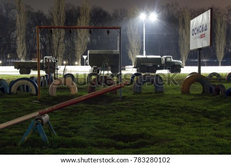 """When the war is near. Military cars on the streets of a peaceful city on the background of a children's playground. The inscription on the board """"The basis of the party of business people"""" #783280102"""