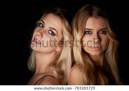 beautiful mother and daughter portrait in Studio on black background. Look great. Professional makeup #783283729