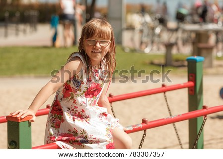 Active kids, outdoor fun concept. Little toddler girl in floral dress playing outside on playground during summertime. #783307357