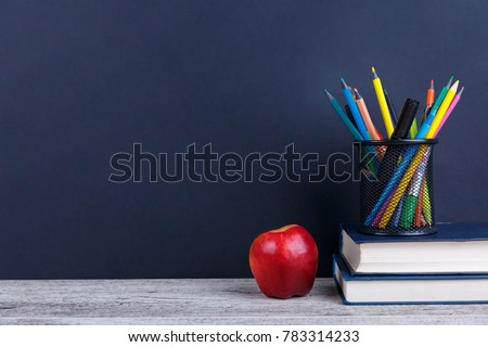 A stack of books, a red apple and colorful pencils in a case, on a dark background with a place for inscription. #783314233