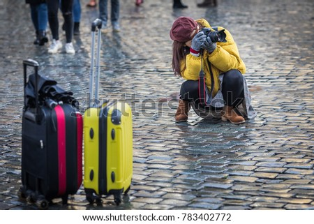 An identified young woman visiting Europe is looking for a better viewpoint for taking a photograph. Travel photography and tourism concepts.