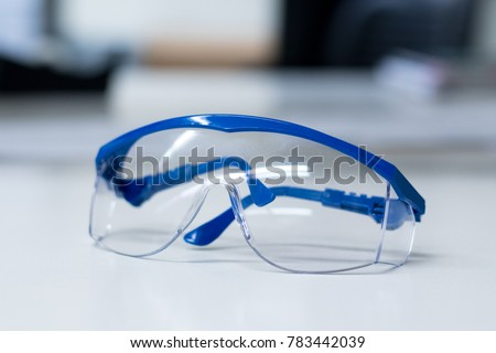 Close-up of blue safety goggles on a desk in a research lab. Royalty-Free Stock Photo #783442039