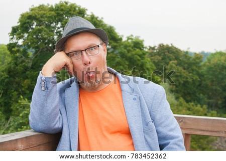 Portrait of a handsome man in orange t-shirt, blue jacket and hat #783452362