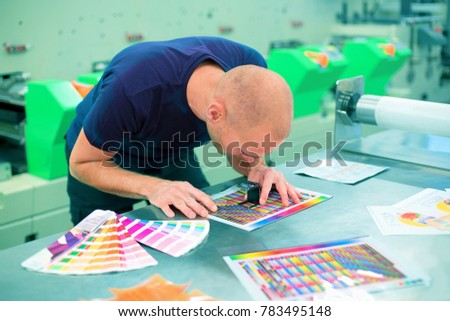 Worker in a printing and press center uses a magnifying glass to check the print quality. Scene showing the print quality control check.