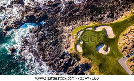 Drone view of a golf course next to the ocean with waves hitting the rocks on the seashore #783497188